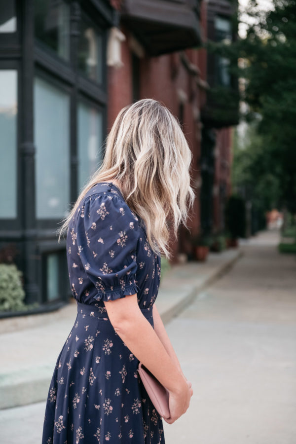 Jessica Sturdy with rooty ombre blonde hair with loose waves wearing a blue floral dress.