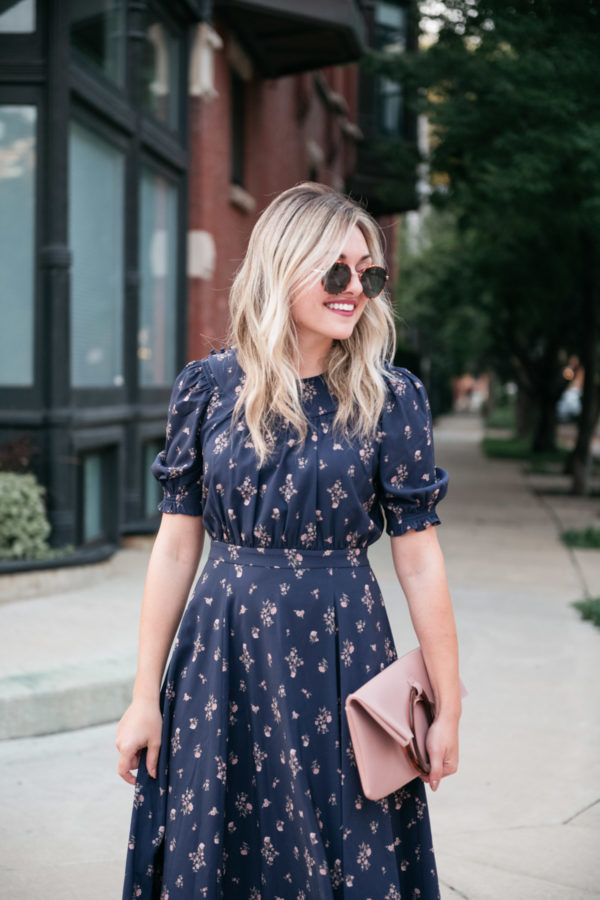 Bows & Sequins wearing a blue and pink floral dress by Gal Meets Glam with a Topshop foldover clutch and round tortoise sunglasses.