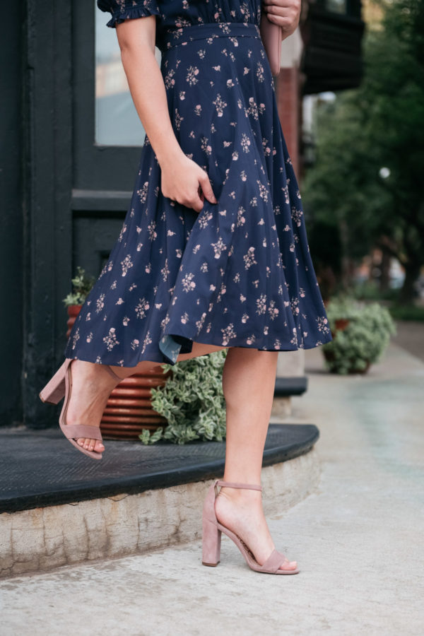 Bows & Sequins wearing a navy blue floral midi dress with blush pink ankle-strap sandals.