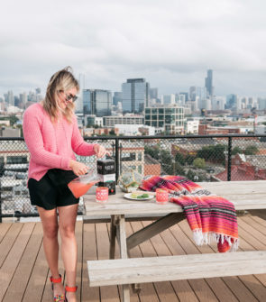 Chicago food and lifestyle blogger Jessica Sturdy of Bows & Sequins pouring a spicy watermelon margarita on a gorgeous rooftop with Chicago skyline views. She's wearing a pink J.Crew sweater, black shorts, and Kat Maconie colorful heels.