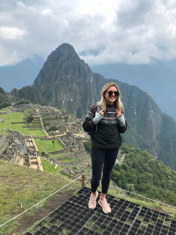 Jessica Sturdy at Machu Picchu in Peru wearing a Peruvian alpaca sweater, Lululemon leggings, Le Specs Prince aviators in matte black, and adidas Ultra Boost sneakers.