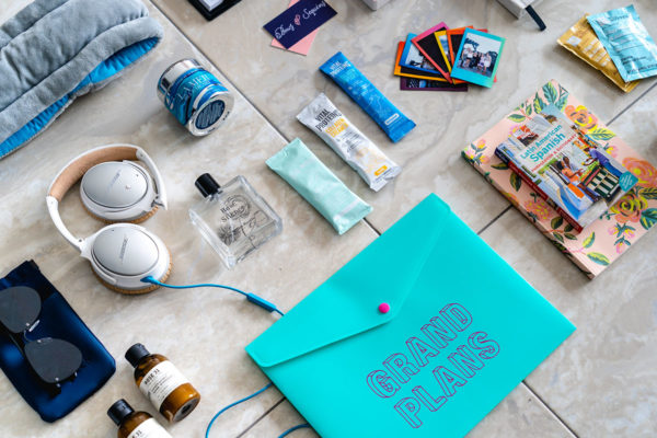 Beauty blogger Jessica Sturdy of Bows & Sequins shares her must-haves for long term travel: Miller Harris Rose Silence perfume, Le Labo Rose 31 bath products, Vital Proteins collagen peptides, collagen creamer for coffee, and beauty water, plus a Grand Plans folder to keep it all organized, and mini polaroid pictures.