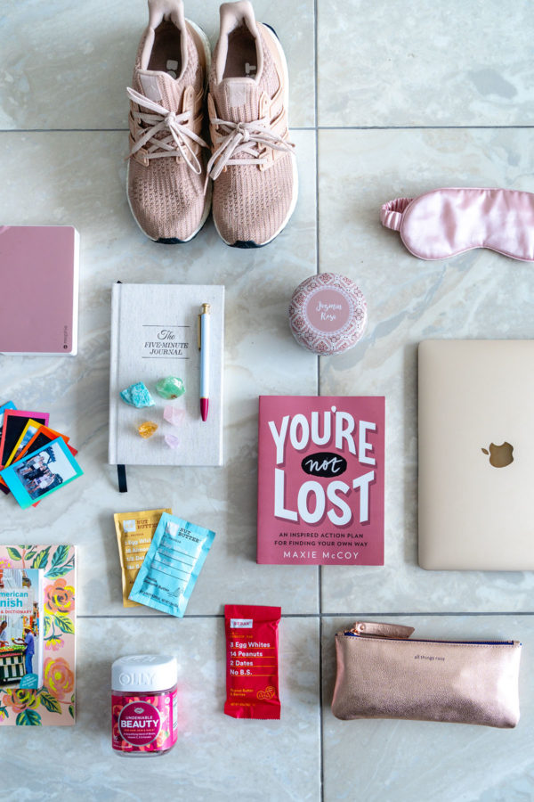 Health and wellness blogger Jessica Sturdy of Bows & Sequins shares a few of her favorite items that she packed for Remote Year: You're Not Lost book by Maxie McCoy, blush pink adidas Ultra Boost sneakers, a rose candle, a rose gold Mophie phone charger, a gold MacBook, a millennial pink eye mask, the 5 Minute Journal, and RXBar's new Peanut Butter & Jelly flavor, and more.