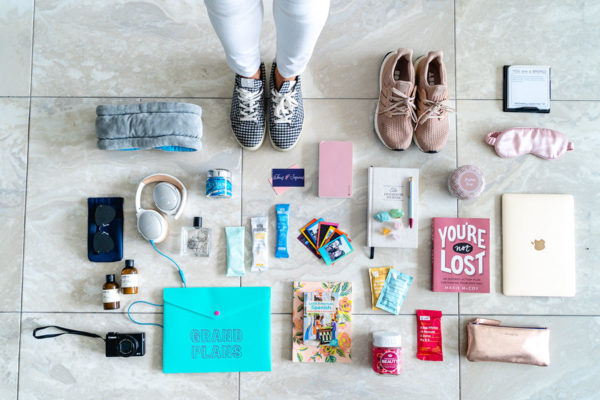 Fashion and travel blogger Jessica Sturdy of Bows & Sequins shares a packing flat lay photo for what she brought along on Remote Year. She's wearing gingham sneakers and standing in the photo with white jeans surrounded by Bose headphones, books, vitamins, RXBars, polaroid photos, and other wellness items that focus on fitness and mindfulness.
