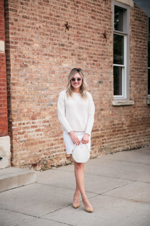 Bows & Sequins wearing a Goat Fashion sweater, Vineyard Vines white denim skirt, nude pumps, and a round handbag.