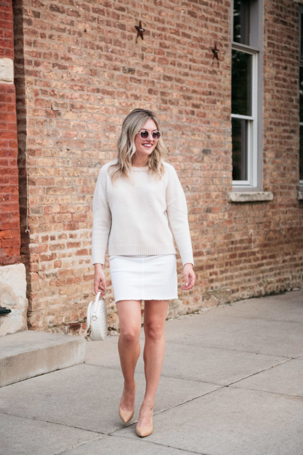 Jessica Sturdy wearing a white and cream monochromatic outfit after Labor Day. Jessica is styling a Goat Fashion cashmere sweater, white denim mini skirt from Vineyard Vines, a round embossed handbag by Brahmin, and Inez heels.