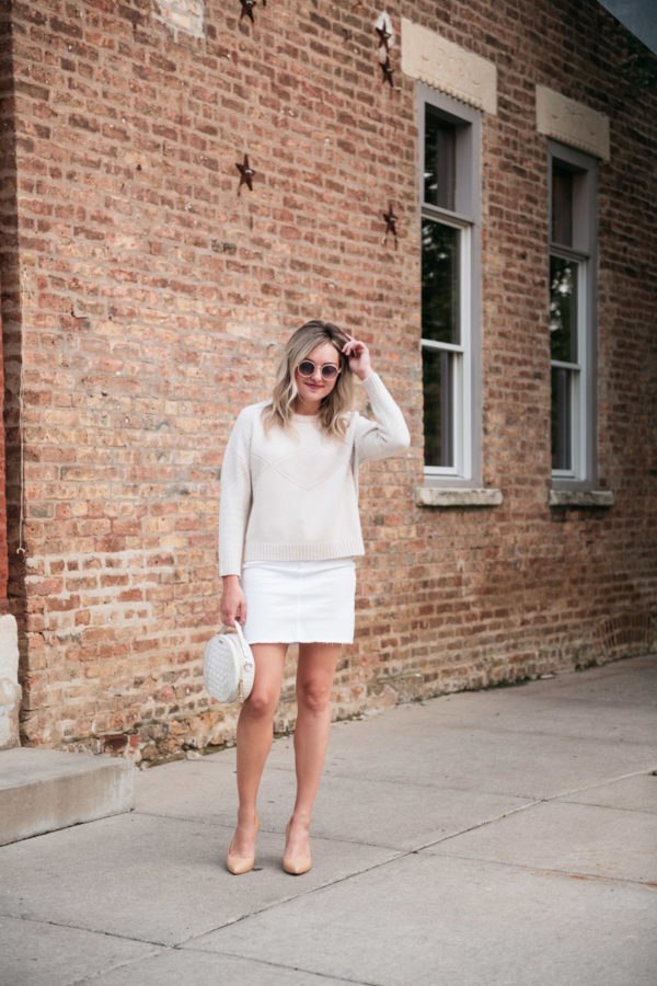 Bows & Sequins styling a cashmere sweater with a white denim skirt for a cute fall outfit.