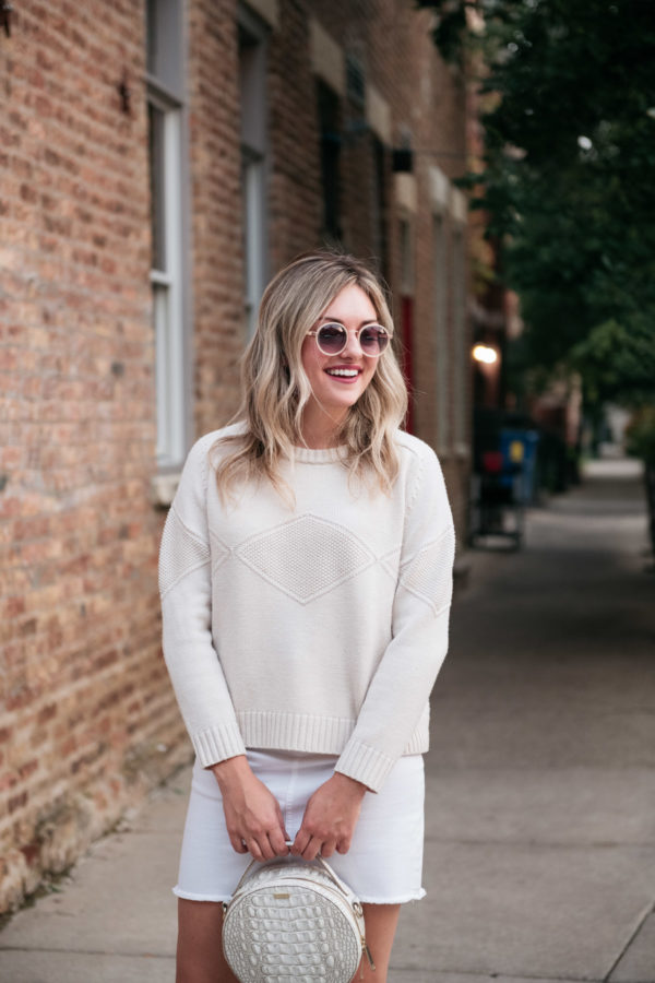 Chicago blogger Bows & Sequins wearing a Goat Fashion cashmere sweater and a white circle handbag.