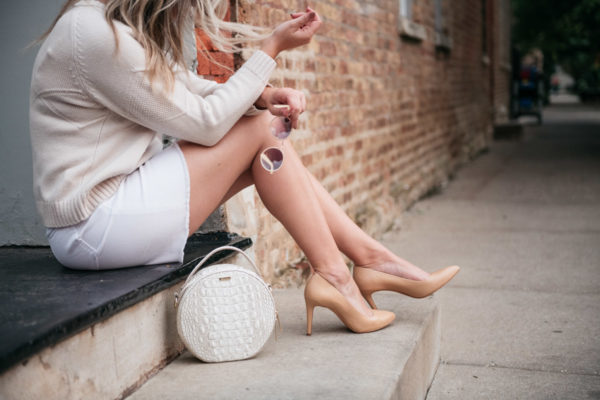 Fashion blogger Jessica Sturdy styling a white denim skirt for fall.