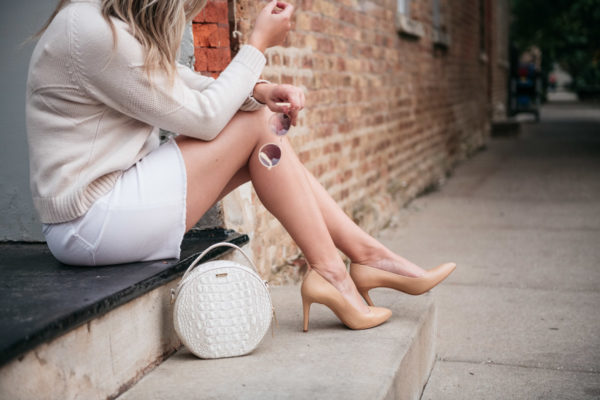 Chicago fashion blogger Jessica Sturdy styling a white denim skirt with nude heels and a circle handbag.