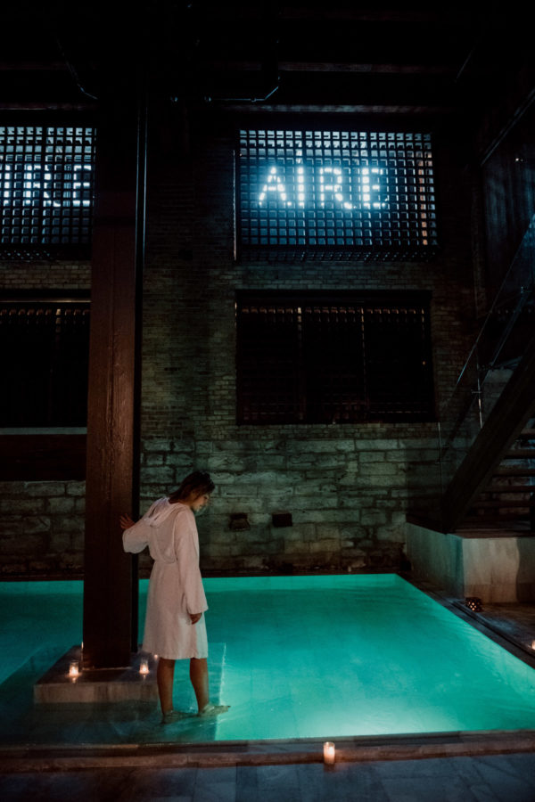 Travel blogger Jessica Sturdy at the Chicago location of AIRE Ancient Baths in a white robe.