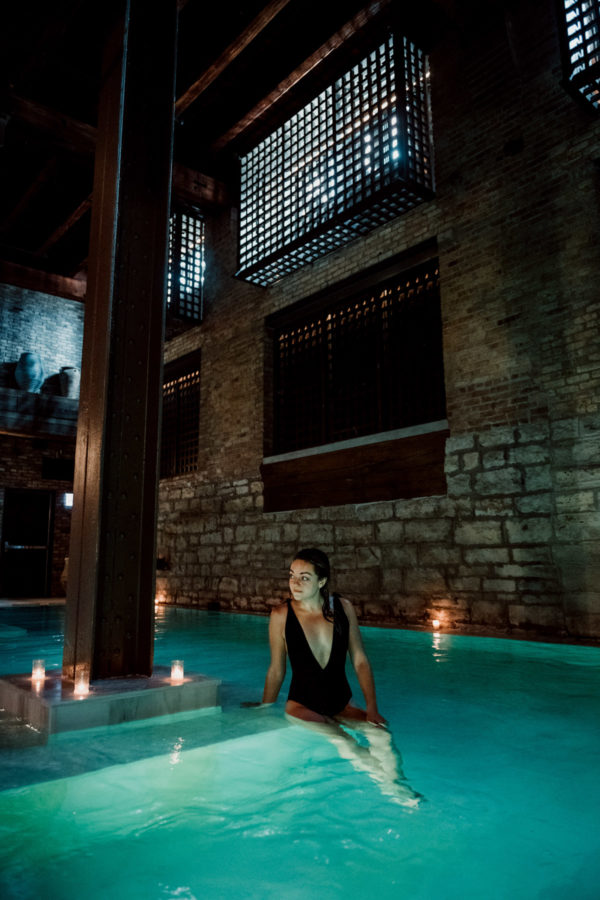 Fashion blogger Jessica Sturdy wearing a black Aerie Deep V One Piece Swimsuit at AIRE Ancient Baths in Chicago.