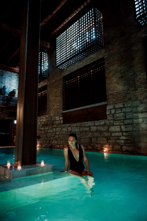 Lifestyle blogger Jessica Sturdy wearing a black one piece swimsuit at AIRE Ancient Baths in Chicago.
