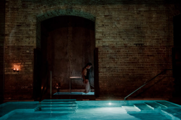 Fitness blogger Jessica Sturdy of Bows & Sequins in the Frigidarium cold plunge pool at AIRE Ancient Baths in Chicago.