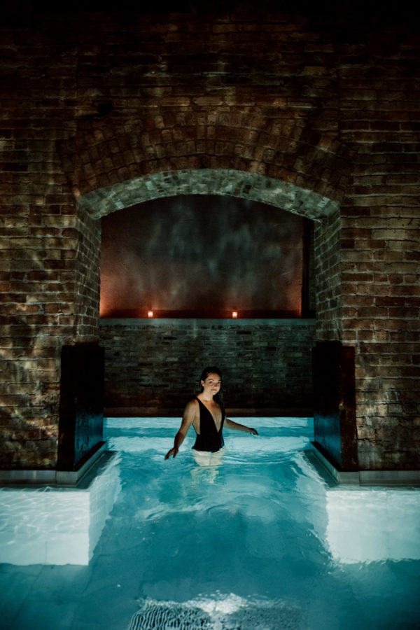 Jessica Sturdy wearing a low cut black swimsuit at AIRE Ancient Baths in Chicago
