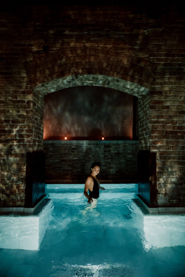 Jessica Sturdy wearing a black one piece swimsuit at AIRE Ancient Baths in Chicago.