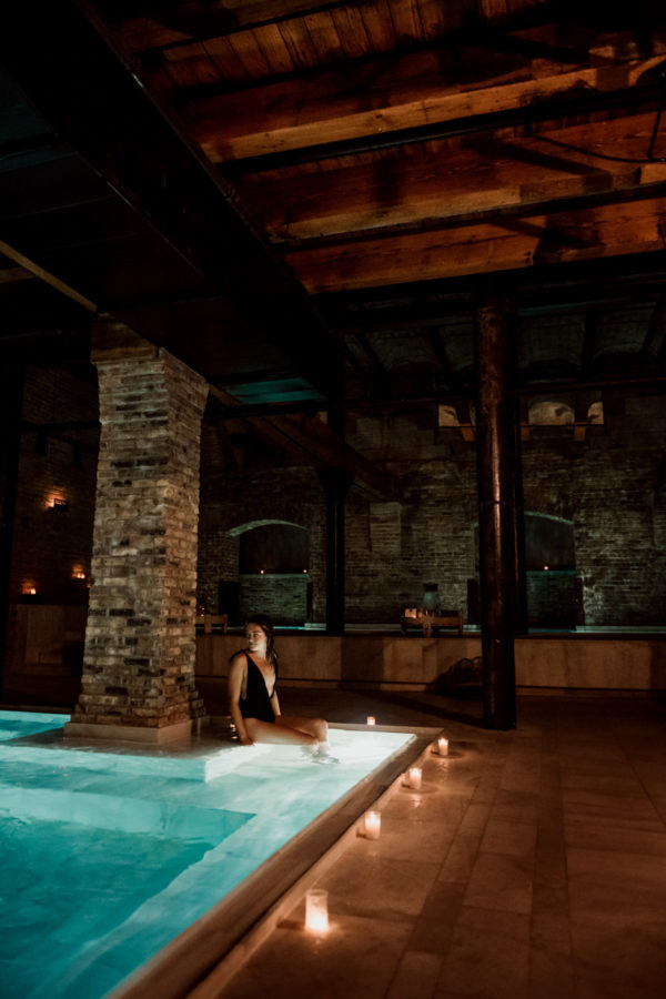 Blogger Jessica Sturdy of Bows & Sequins relaxing at AIRE Ancient Baths in Chicago in a black swimsuit.