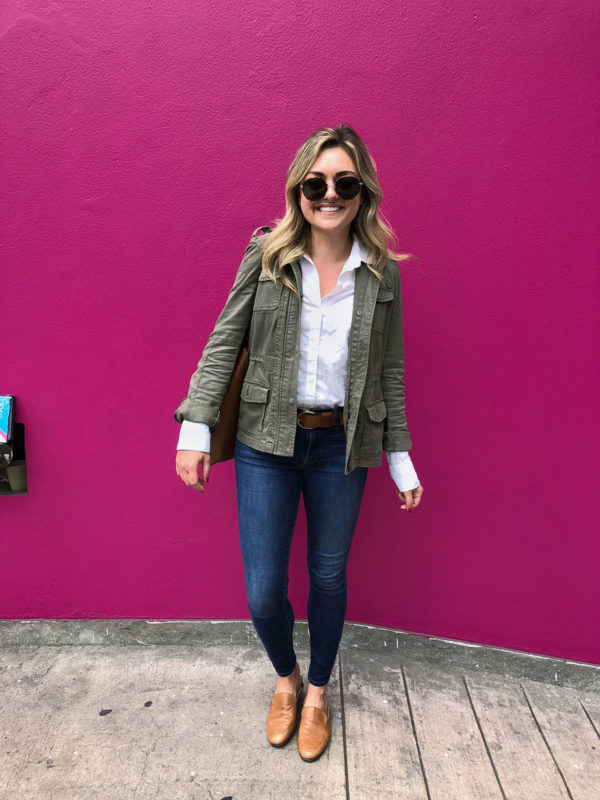 Jessica Sturdy of the fashion blog Bows & Sequins wearing an army green jacket, white button front shirt, and leather loafers in Lima Peru in front of a pink wall.