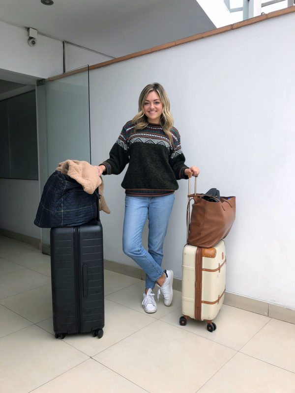 Jessica Sturdy on Remote Year Transition Day in Lima Peru. Jessica is wearing a Peruvian sweater, Mott & Bow mom jeans, and Stan Smith sneakers with a large black Away suitcase and a carry-on Bric's Bellagio cream spinner suitcase.