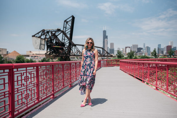 Chicago fashion blogger Bows & Sequins wearing a floral high-low dress with pink heels.