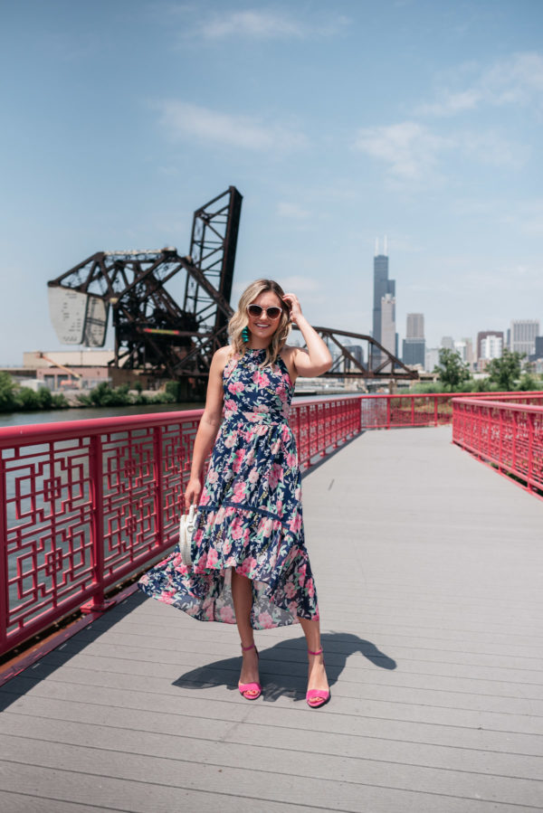 Chicago style blogger Bows & Sequins wearing a pink and navy floral dress in front of the skyline.