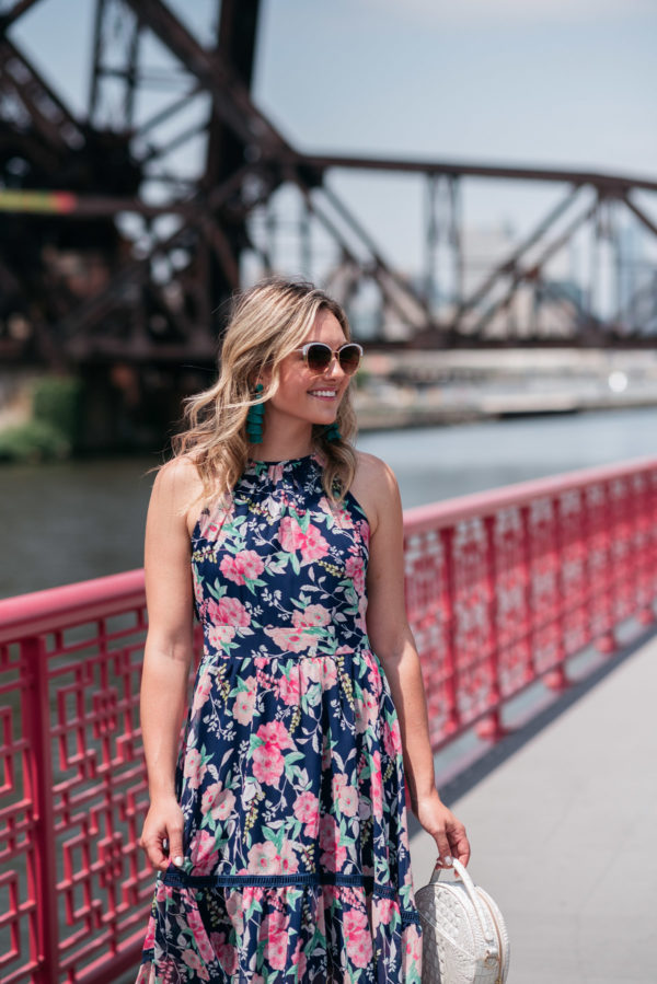 Chicago blogger Jessica Sturdy wearing a pink and navy floral dress by Eliza J with Bauble Bar earrings.