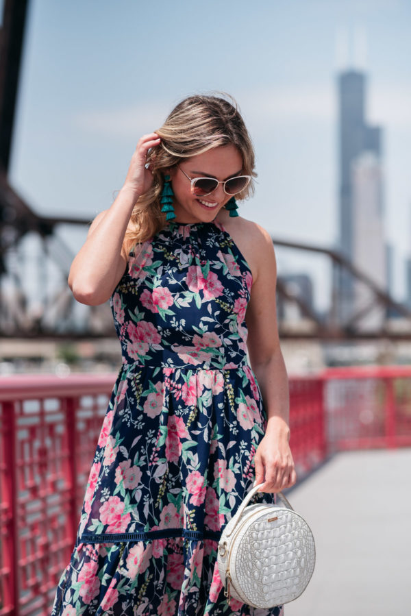 Fashion and beauty blogger Bows & Sequins styling a floral dress with BaubleBar tassel earrings.