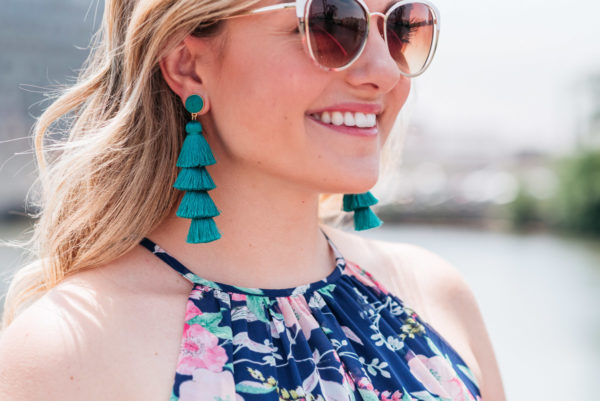 Bows & Sequins wearing white and gold cateye sunglasses with teal tassel earrings.