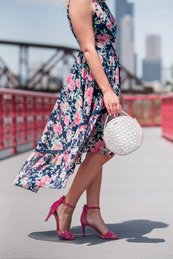 Chicago beauty blogger Bows & Sequins wearing a floral Eliza J dress with a high-low hem, pink ankle strap heels, and a round white handbag by Brahmin.