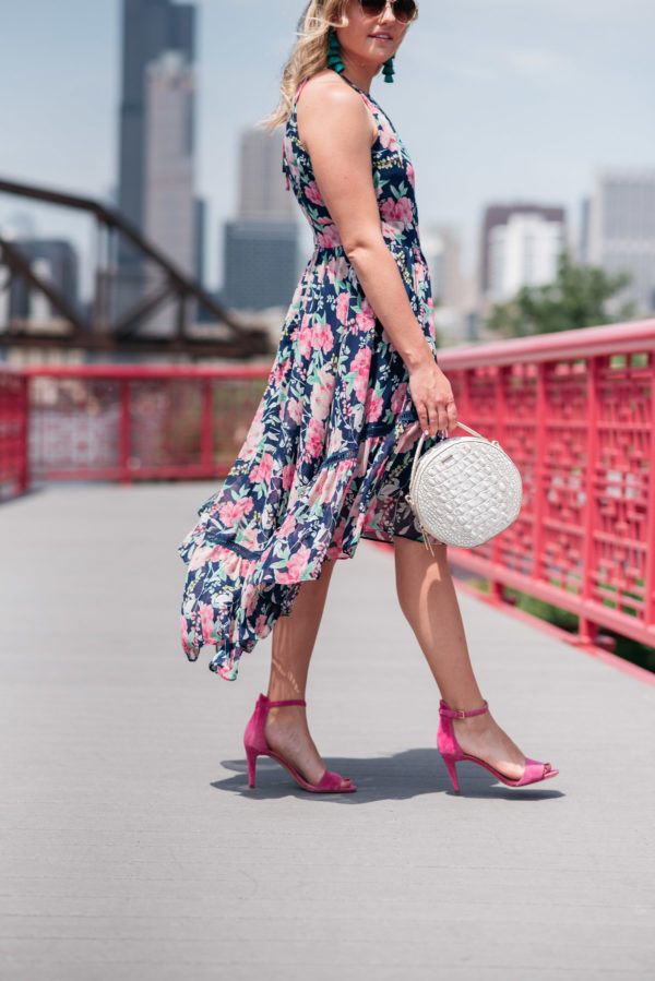 Chicago lifestyle influencer Bows & Sequins wearing a navy and pink floral dress with a high-low hem, pink ankle strap sandals, and a round white handbag.