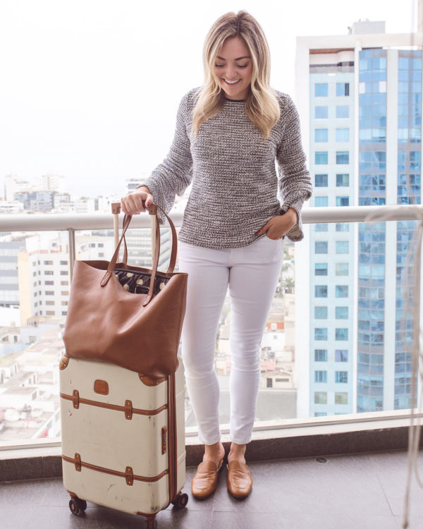 Travel blogger Jessica Sturdy of Bows & Sequins in Lima Peru wearing a tweed Sail to Sable top, white jeans, and leather loafers. She's carrying a Bric's Bellagio Carry-On Spinner Suitcase with a monogrammed leather Cuyana tote.