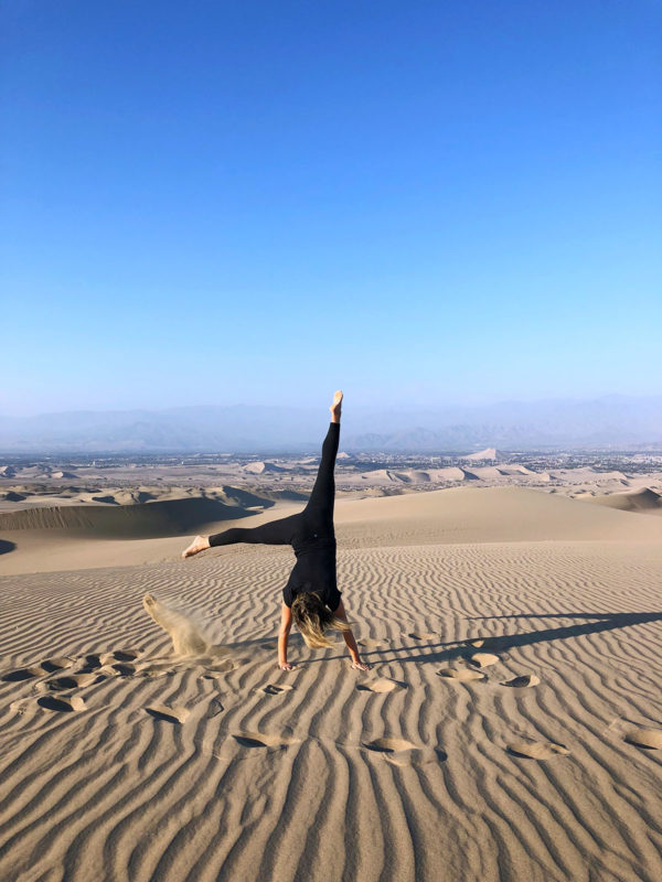 Women's travel blogger Jessica Sturdy of Bows & Sequins doing a cartwheel in the sand dunes of Huacachina in Peru.