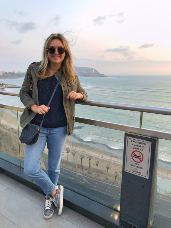 Travel lifestyle blogger Bows & Sequins wearing a green army jacket, navy blue sweater, navy Gucci bag, and gingham sneakers. She's standing at Larcomar in Lima, Peru with the beach, ocean, and sunset int he background.