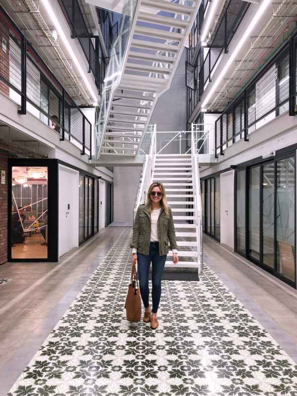 Women's lifestyle blogger Jessica Sturdy of Bows & Sequins at Comunal Coworking Barranco in Lima, Peru. She's wearing an olive green jacket, cream sweater, Frame skinny jeans, and leather slip-on loafers with a Cuyana leather tote.