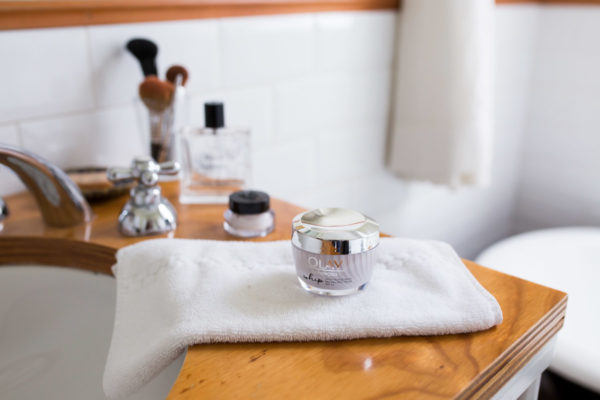 Olay Whips Moisturizer on a bathroom vanity counter with makeup brushes and perfume.