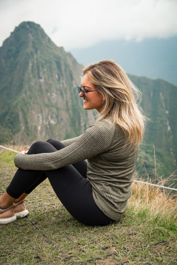 Women's US-based travel and lifestyle blogger Jessica Sturdy of Bows & Sequins at Machu Picchu in Peru wearing lululemon and adidas Ultraboost sneakers.