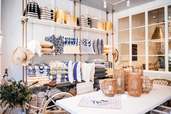 Lifestyle influencer Bows & Sequins takes a picture of the market in the front of the new Serena & Lily shop on Armitage in Chicago. Colorful blue and yellow totes, towels, pillows, and bags mixed along with natural rattan elements.