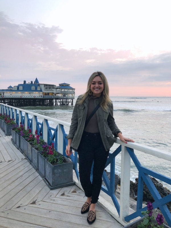 Women's lifestyle blogger Bows & Sequins in Lima, Peru at La Rosa Nautical on the water. Jessica is wearing a green jacket, black jeans, and leopard print loafers.