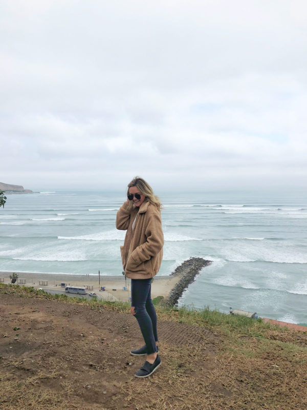 Travel influencer Bows & Sequins on the cliffside in Lima, Peru wearing a camel teddy coat and black jeans with Joie sneakers.