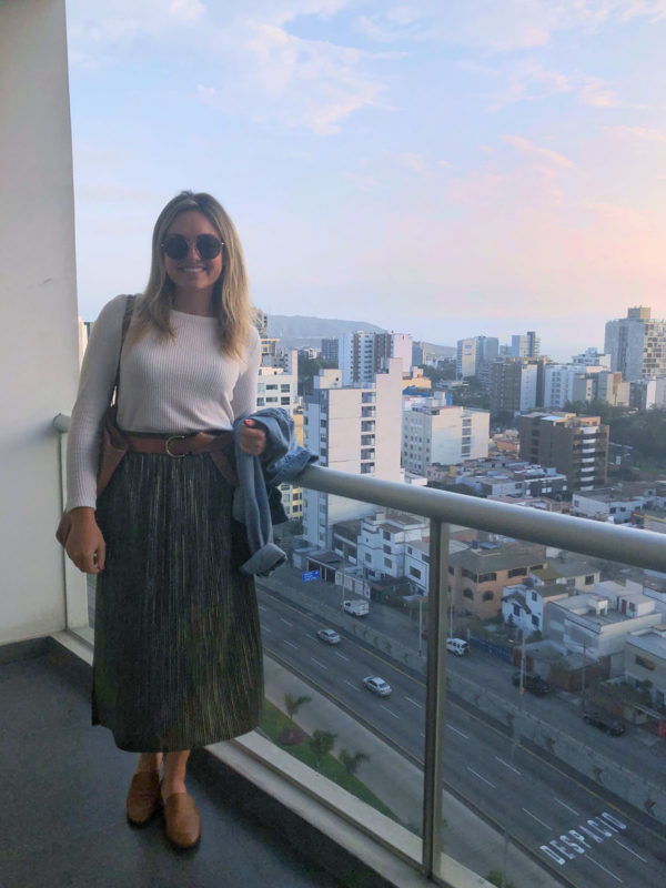 Remote Year blogger Bows & Sequins wearing a pleated green skirt and cream sweater with leather accessories on her apartment balcony in Miraflores, Lima, Peru.