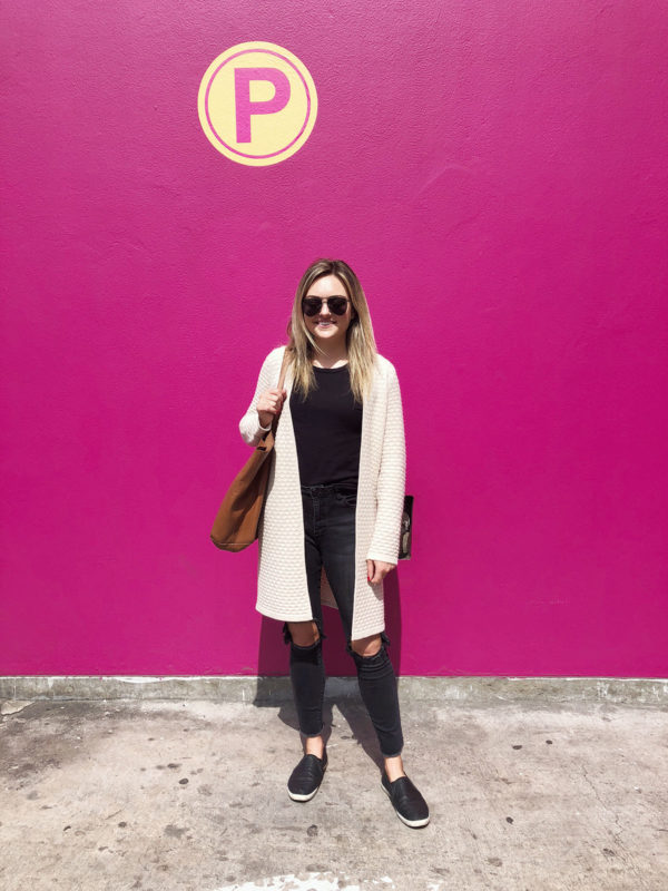 Bows & Sequins wearing a Sail to Sable honeycomb cashmere cardigan, black tee, jeans, and sneakers, with Le Spec Prince Aviator sunglasses in front of a pink wall in Lima, Peru.