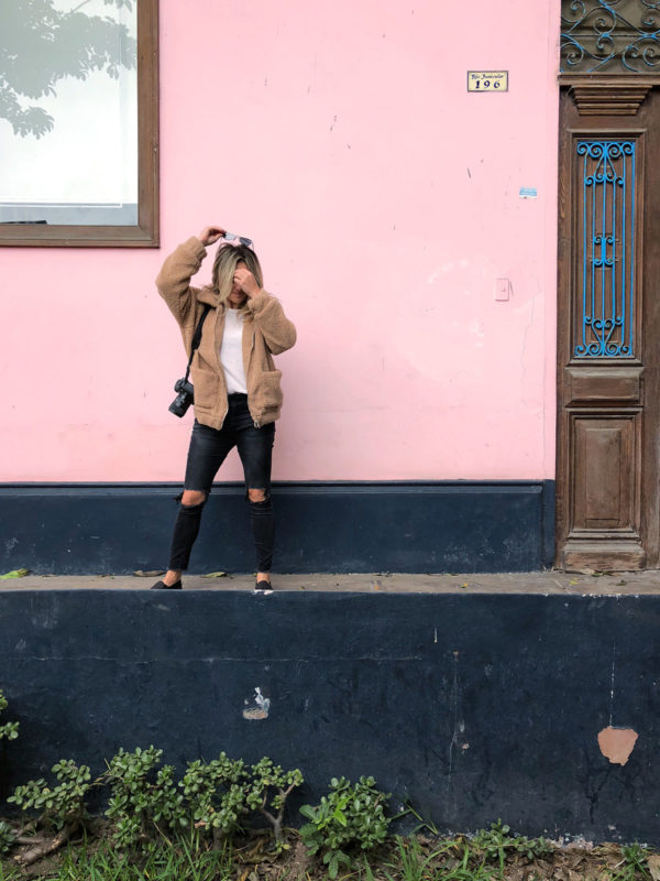 Travel instagrammer Jessica Sturdy of Bows & Sequins in front of a pink and blue wall in Barranco, Lima, Peru. Jessica is wearing a camel teddy coat, sneakers, and black ripped One Teaspoon jeans with a Canon 5D Mark iii.