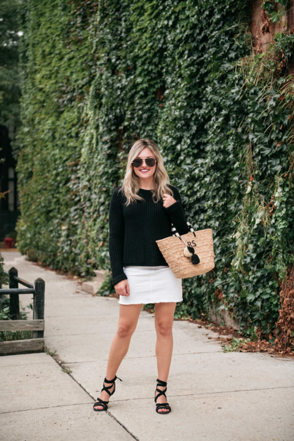 Chicago personal stylist Jessica Sturdy wearing a white denim skirt with black accessories and a straw bag.