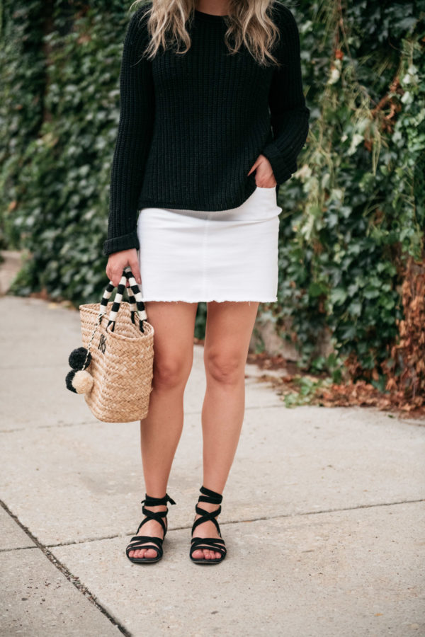 Chicago blogger Jessica Sturdy of Bows & Sequins wearing a white denim skirt, black sweater, lace-up sandals from M. Gemi, and a Kayu Designs pom pom tote.