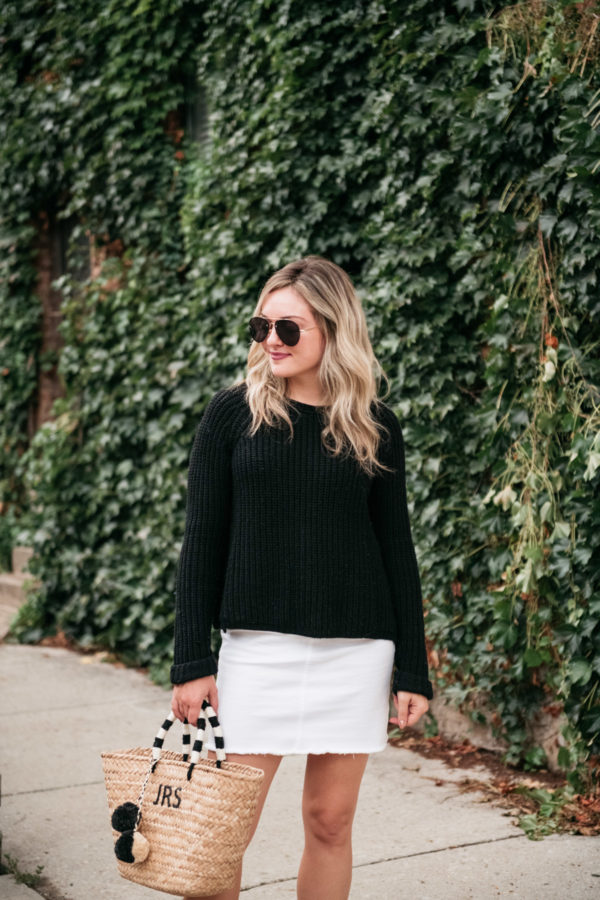 Chicago beauty blogger Jessica Sturdy wearing a white denim skirt with a straw bag and black aviators.