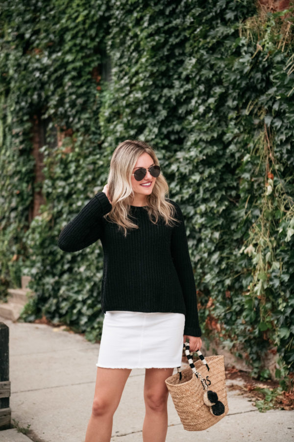 Chicago blogger Jessica Sturdy styling a black sweater with a white denim mini skirt and a straw tote.