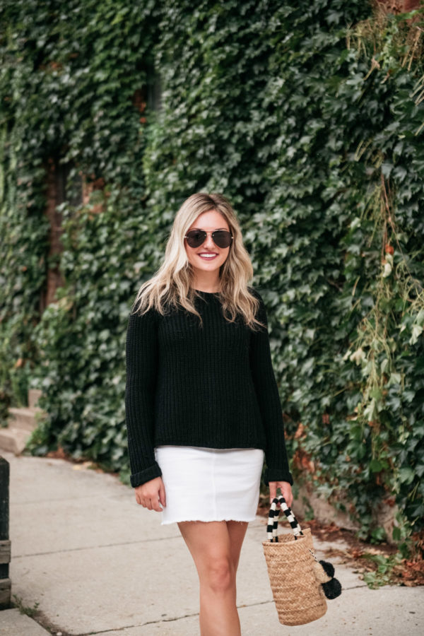 Chicago travel blogger Jessica Sturdy of Bows & Sequins styling a black sweater with a white skirt for a cute fall outfit.