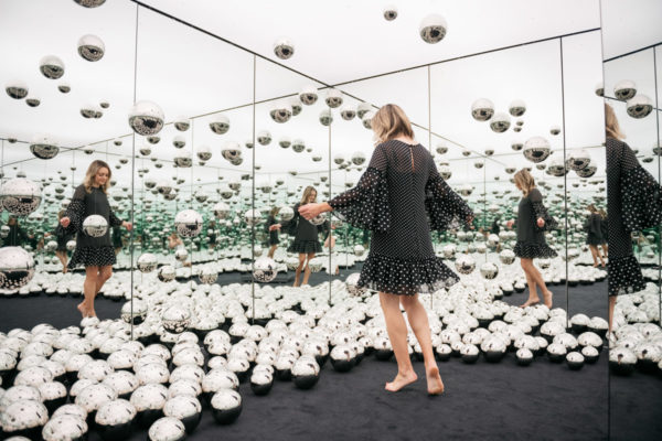 Chicago travel blogger Jessica Sturdy of Bows & Sequins wearing a polka dot bell sleeve dress in the Infinity Mirrors art exhibit.