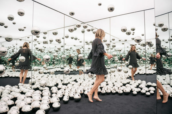Chicago lifestyle blogger Jessica Sturdy of Bows & Sequins wearing a polka dot dress at the Infinity Mirrors room exhibit with the glass orbs.