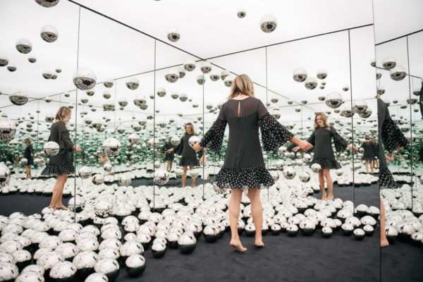 Chicago influencer Jessica Sturdy of Bows & Sequins twirling barefoot in the Infinity Mirror room art installation.